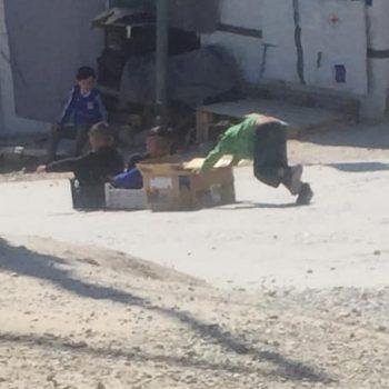 Kinder in Moria spielen mit selbstgebauten Schlitten